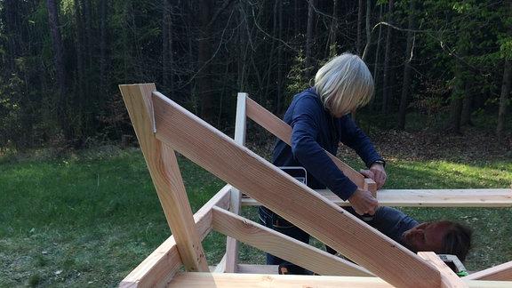 Blick auf eine Holzkonstruktion. Ein Mann arbeitet am hinteren Teil der Konstruktion.