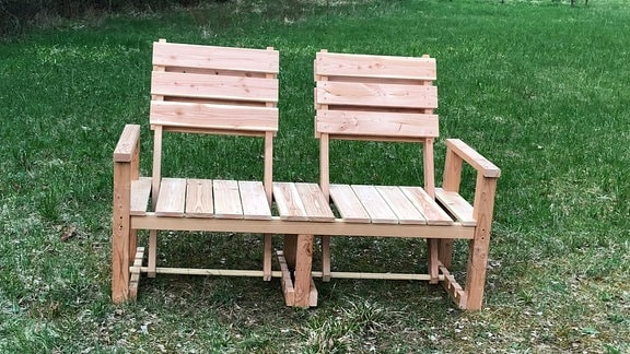 Eine Holzbank für zwei Personen mit verstellbaren Lehnen.