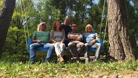 Vier Menschen sitzen auf einer an Bäumen befestigten, hängenden Gartenschaukel. Ein weiterer Mann steht dahinter.