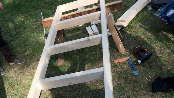 Eine Holzkonstruktion liegt auf Malerbänken.