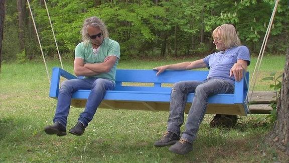 Zwei Männer auf selbstgebauter Gartenschaukel