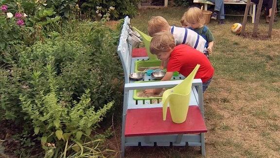 Kinder spielen an einer Matscheküche