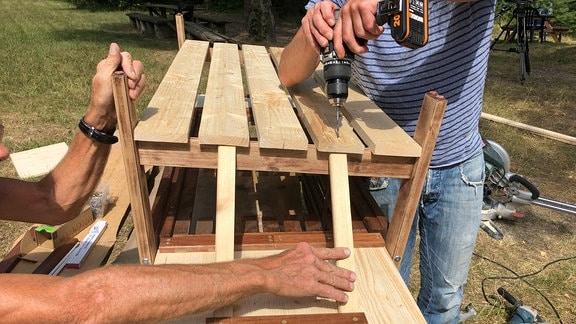 Aus einer Holzbank wird mit Hilfe von Brettern eine Matschküche für Kinder im Garten gebaut