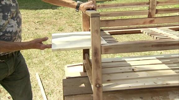 Aus einer alten Sitzbank und Holzbrettern wird ein Matschplatz für Kinder im Garten gebaut
