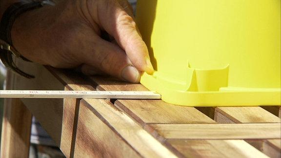 Beim Bau einer Matschküche für Kinder wird ein Zollstock auf der Sitzfläche einer Holzbank neben eine Schüssel aus gelbem Kunststoff gehalten