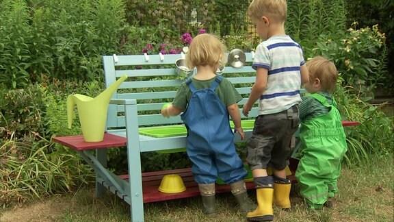Kinder in Matschhosen und Gummistiefeln spielen an einer bunt bemalten Holzbank, die zu einem Matschplatz umgebaut wurde