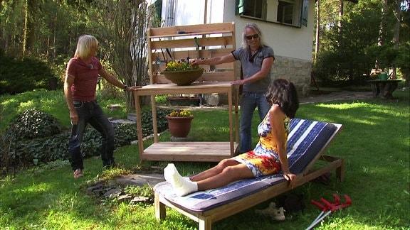 Eine Frau auf einer Liege im Garten dreht sich zu zwei Männern um, die hinter ihr neben einer selbstgebauten Pflanzstation aus Holz stehen