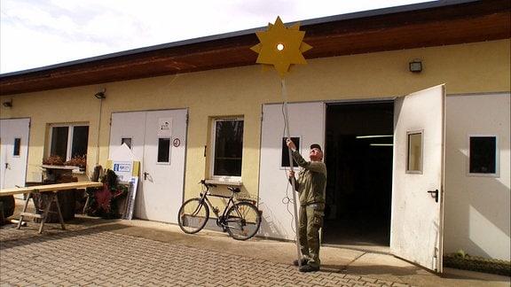 Der MDR Gartenmeister Jürgen Meister steht mit einer gelb lackierten Sonne aus Holz mit einem Glühlampe in der Mitte an einem langen Stab vor einem Werkstatt-Gebäude im Egapark in Erfurt