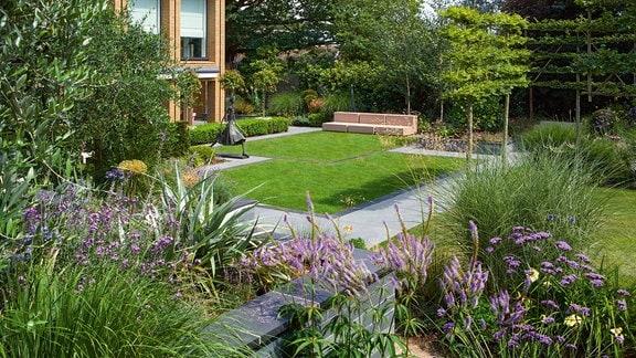 Ein Garten mit Rasenflächen und Staudenbeeten.