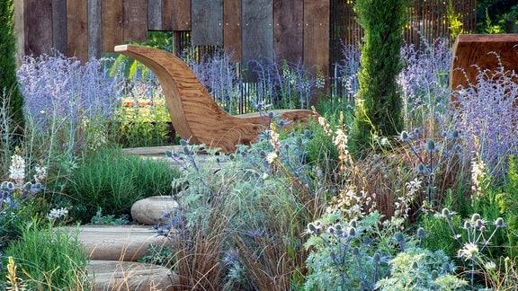 Blaue und weiße Pflanzen schlängeln sich neben Holzstufen entlang durch einen Garten.