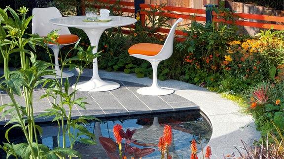 Ein Garten mit Sitzgruppe gestaltet mit Pflanzen in kräftigen Farben.