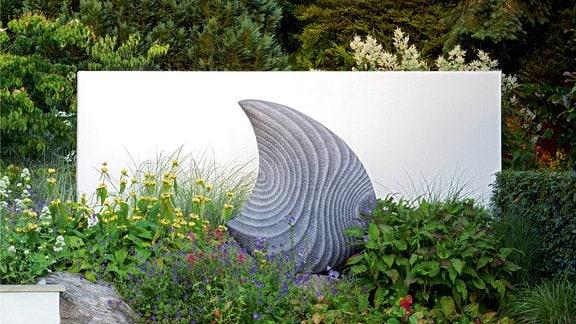Ein großer geschwungener Stein, der aussieht wie ein Tropfen, steht vor einer Mauer in einem Garten.