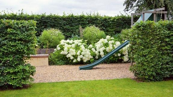 In einem Garten wurde durch mehrere Hecken ein ein Raum für einen Spieleplatz geschaffen.