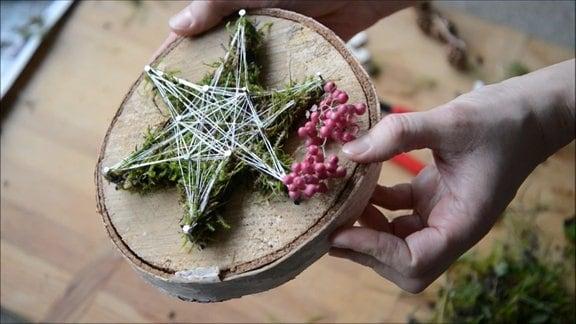Nagelbild auf Baumscheibe mit Moos als Deko