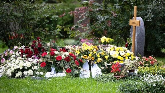 Ein mit vielen Blumen geschmücktes Grab auf einem Friedhof.