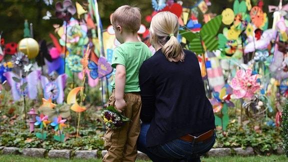 Eine Mutter mit ihrem kleinen Sohn an einer Kindergrabstätte auf dem Friedhof.