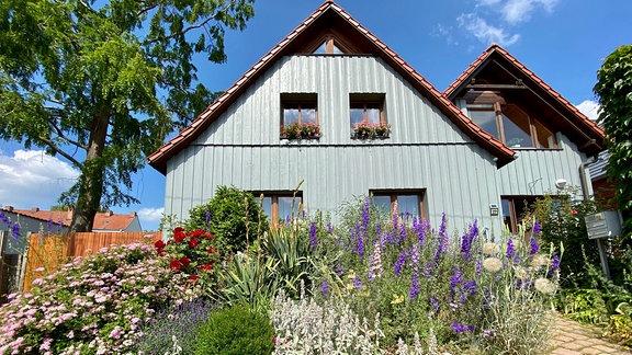 Vor einem blaugrau gestrichenen Einfamilienhaus wachsen Rittersporn, Salbei und viele andere blühende Pflanzen.