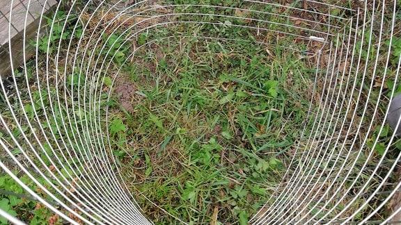Als Zylinder geformte Estrichmatte, die an den Enden mit Kabelbinder zusammengehalten wird.