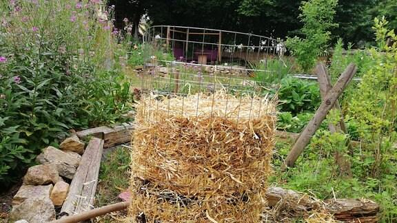 Ein Kartoffelturm von der Seite. Darin sind abwechseln Stroh und Erde gestapelt.