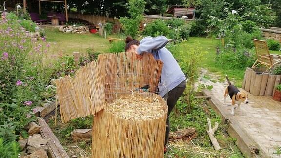 Eine Frau schneidet bei einem Kartoffelturm den überstehenden Rand einer Bambusmatte ab.