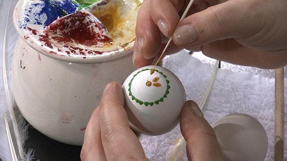 Mit einem Federkiel wird Wachs auf das Ei getupft.