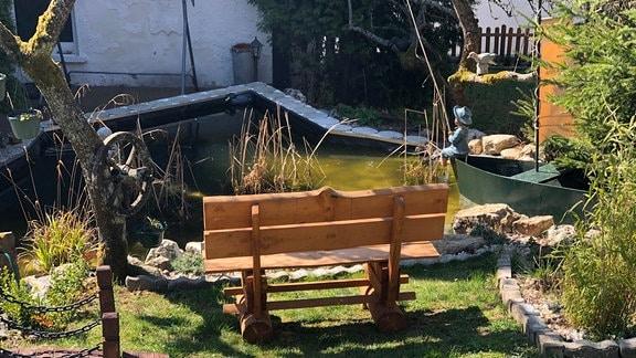 Privatgarten in Südthüringen mit einer liebevoll gestalteten Teichlandschaft und einer Bank.