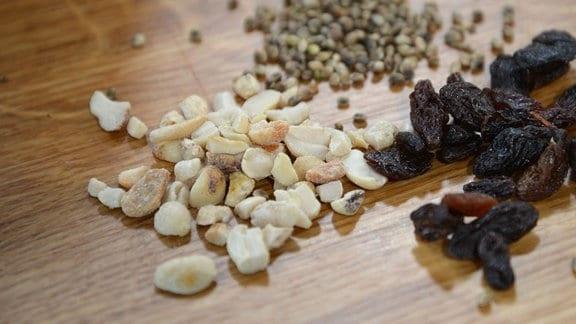 Auf einem Tisch liegen geschälte Erdnüsse, Rosinen und Hanfsamen