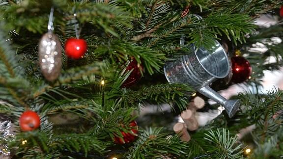 An einem Weihnachtsbaum hängt eine kleine Gießkanne