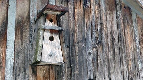 Ein Meisenkasten aus Holz an einer Hauswand.