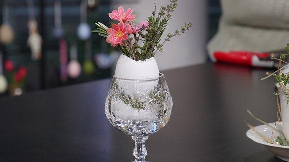 In einem Cognacschwenker voller Kandiszucker steckt ein ausgeblasenes, oben offenes Hühnerei, in dem Triebe von Thymian und Rosmarin sowie eine rosa Blüte arrangiert wurden.