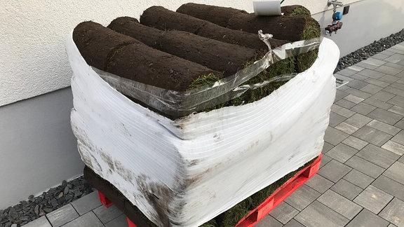 Eine Europalette mit mehreren Bahnen von aufgerolltem Fertigrasen, der von einer weißen Folie umhüllt ist, steht in einer gepflasterten Einfahrt