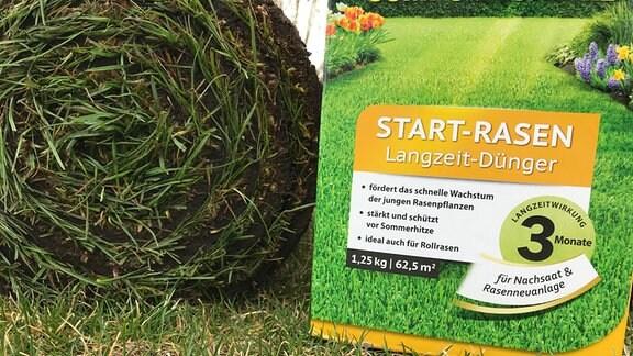 Auf einer Rasenfläche steht ein Pappkarton mit Dünger mit der Aufschrift Start-Rasen neben einer Bahn aufgerollten Fertigrasens