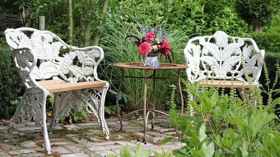Sitzecke mit weißen Gartenstühlen zwischen Bäumen