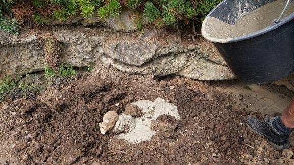 In die Kuhle wird Beton gegossen, auf den Beton werden wieder Steine gelegt