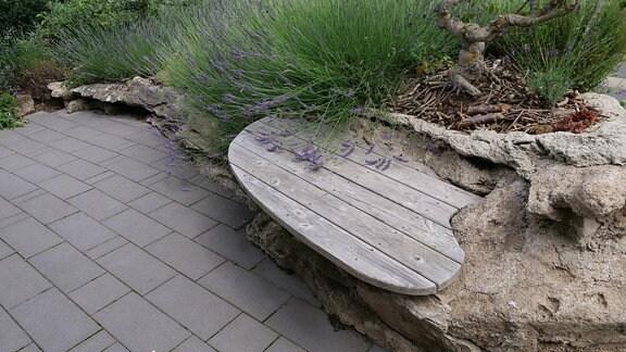 Felsen aus Beton mit eingearbeiteter Sitzplatte aus Holz