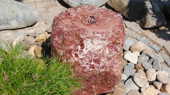Brunnen mit einem unregelmäßig geformten, rötlichen, mit weißen Einschlüssen durchzogenem Stein, aus dem Wasser sprudelt