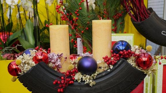 Weihnachtsdeko mit Autoreifen und zwei Kerzen