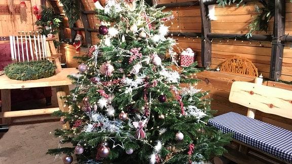 Ein festlich geschmückter Weihnachtsbaum mit rosa, weißem und dunkelviolettem Schmuck.