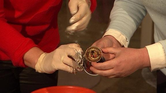 Ein Kerzenhalter wird auf einen Plastikbecher gesteckt