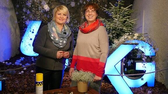 Zwei Frauen stehen hinter einem Tisch mit einer Pflanze und verschiedenen Deko-Materialien. Sie stehen vor einer weihnachtlich dekorierten Fläche.
