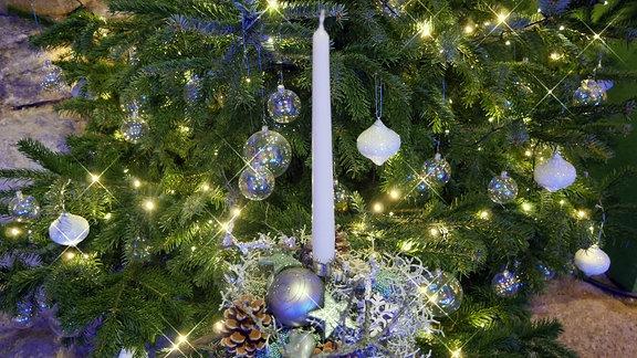Vor einem Weihnachtsbaum steht ein kleiner Tisch mit einem Gesteck, das mit Sternen, einer Weihnachtsbaumkugel und einer Kerze dekoriert wurde.