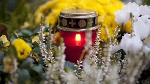 Brennendes Grablicht auf einem Friedhof