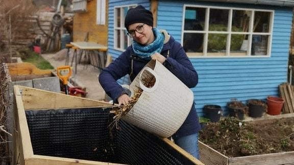 Nadine Witt befüllt ein Hochbeet mit Erde