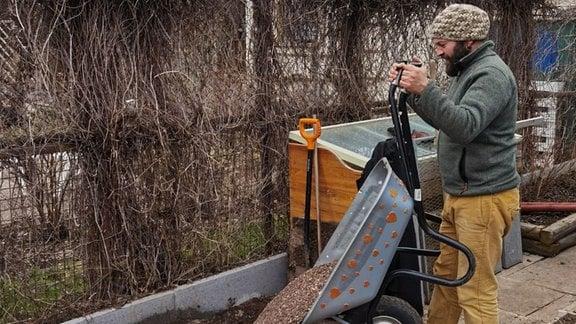 Frank Krause schüttet eine Schubkarre Kies auf ein Beet.