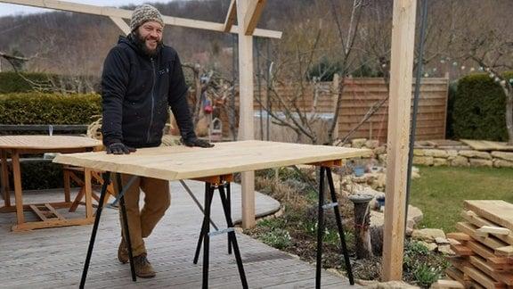 Auf ener Terrasse liegt viel Holz. Frank Krause steht an einem Arbeitstisch.