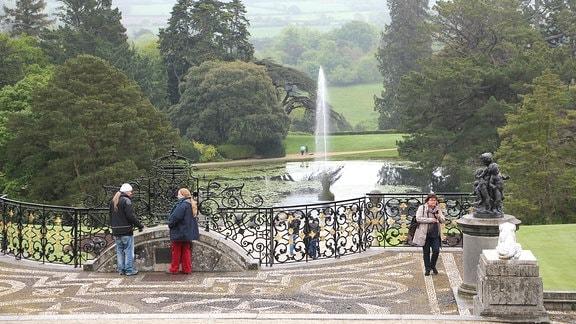 Blick über eine Terrasse in einen Park mit See und Springbrunnen.