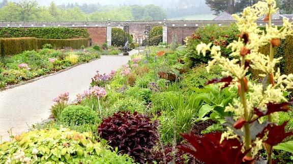 Ein Weg zieht sich durch einen Park. Rechts und links wachsen verschiedenen Pflanzen auf angelegten Beeten.