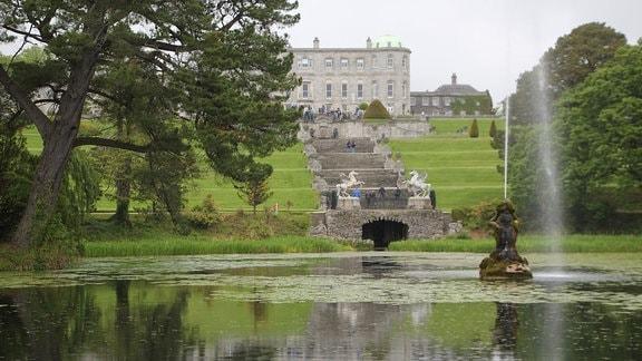 Blick über einen See auf eine Treppe die zu einem Schloss führt.