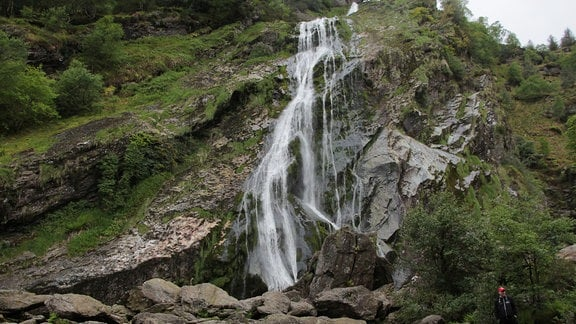 Über einen Berg mit vielen Felsen fließt Wasser ins Tal herunter.
