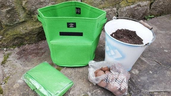 Equipment fürs Kartoffelpflanzen: Pflanzsack, Eimer mit Erde, Kartoffeln